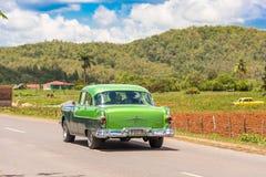 VINALES,古巴- 2017年5月13日:美国绿色减速火箭的汽车沿路乘坐 复制文本的空间 免版税图库摄影