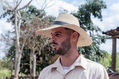 VINALES,古巴- 2018年3月14日 有一个白色帽子的古巴人在烟草农场 图库摄影