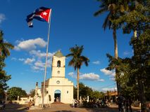 Main square with Church and cuban flag at  vinales with tourist. Vinales, Cuba - December 5, 2017: Main square with Church and cuban flag at  vinales with Royalty Free Stock Images