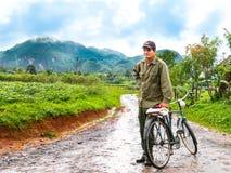 Vinales, Kuba Juni 2016: Kubanischer Mann mit dem Fahrrad, kommend von den Tabakplantagen zurück, umgeben durch grüne Felder stockbilder