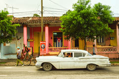 Vinales main road, Cuba. Old car situated in front of a cuban flag, in Vinales centre stock photo