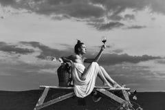 Vinannonseringbegrepp Vindegustatin Nätt kvinna med vin över himmel Arkivfoton