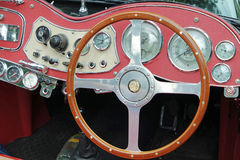 Vinatge dashboard on an open top sports car. Old vintage open top car showing the wooden steering wheel, speedometer, rev counter, temp gauge and switches. red Royalty Free Stock Photography