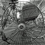 Vinatge Tricycle Wheel. Vintage Tricycle Wheel in close-up. With a basket on the back, spring saddle, solid tires. Bicycle Royalty Free Stock Images