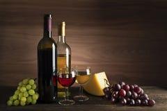 Vinbootle och exponeringsglas med mat på trätabellen arkivfoton
