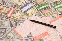 Vinca la lotteria Biglietto e matita di lotteria sul fondo del dollaro Fotografie Stock