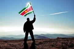 Vincitore dell'uomo che ondeggia la bandiera del Surinam Fotografie Stock