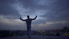 Vincitore nella vita che gode del paesaggio urbano di notte, raggiungente gli scopi, direzione personale stock footage
