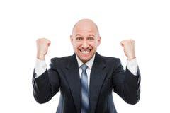 Vincitore sorridente dell'uomo d'affari che gesturing il pugno alzato delle mani che celebra risultato di vittoria immagini stock