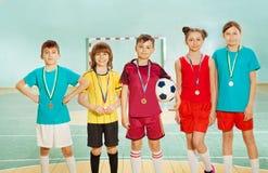 Vincitori di calcio che stanno in conformità con le medaglie fotografia stock