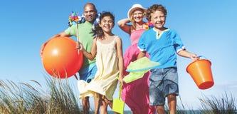 Vinculación alegre de la familia por el concepto del día de fiesta de la playa Imagenes de archivo