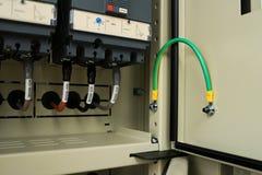 Vinculación de tierra para la puerta del panel eléctrico imagen de archivo
