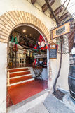 Vind charmante koffie, winkels, & hier, een verrukkelijke wijnopslag met de ingang van de baksteenboog in smalle steeg Stock Afbeeldingen