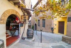 Vind charmante koffie, winkels, & hier, een verrukkelijke wijnopslag met de ingang van de baksteenboog in smalle steeg Stock Fotografie
