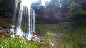 Vind vinkar gräsflickan rymmer pranayamayoga poserar på vattenfallet stock video