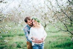 Vinda da mola! Homem e mulher gravida alegres novos bonitos dos pares em flores da grinalda na cabeça que abraça no jardim da árv fotos de stock royalty free