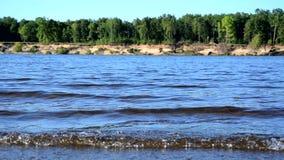 Vinden kör vågorna på floden, sjön, vågor på en sandig strand lager videofilmer