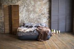 Vinden rummet med en grå säng på ett trägolv med gråa väggar, stearinljus och trälandskap arkivfoton