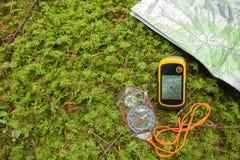Vindend de juiste positie in het bos met een kompas, breng in kaart stock afbeelding