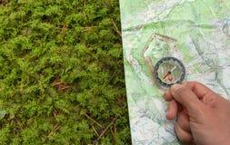 Vindend de juiste positie in het bos met een kompas, breng in kaart royalty-vrije stock foto
