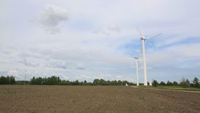 Vindgeneratorer, som frambringar elektricitet från vinden på fältet, rotation från vinden, naturlig makt, bransch stock video