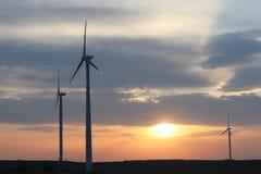 Vindkraftstation i solnedgången Roterande blad av energigeneratorer Ekologiskt ren elektricitet Moderna teknologier för t Fotografering för Bildbyråer