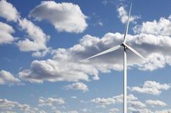 Vindkraftväxt mot vita pösiga moln Arkivfoto