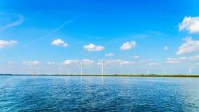 Vindlantgård med två och tre bladed vindturbiner längs kusten av Veluwemeer royaltyfri fotografi
