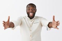 Vindo em meus braços Retrato do homem afro-americano considerável amigável e feliz alegre com barba e corte de cabelo curto imagem de stock