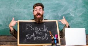 Vindo a nós Os alunos novos das boas vindas do professor entram na instituição educativa O professor ou o diretor de escola dão b foto de stock