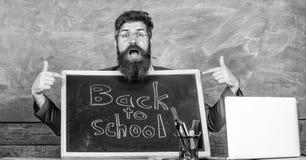 Vindo a n?s Os alunos novos das boas vindas do professor entram na institui??o educativa O professor ou o diretor de escola d?o b imagem de stock