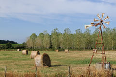 Vindpump och höstackar i ett fält Arkivfoton