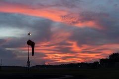 Vindsocka under på gryningen under den röda orange glödande himlen med cirrusmoln- och stackmolnmoln arkivfoto