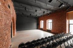 Vindstil Hall med svartstolar för webinars och konferenser Ett enormt rum med stora Windows som omges av murverk arkivbilder