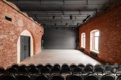Vindstil Hall med svartstolar för webinars och konferenser Ett enormt rum med stora Windows som omges av murverk royaltyfri bild