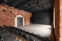 Vindstil Hall med svartstolar för webinars och konferenser Ett enormt rum med stora Windows som omges av murverk arkivbild