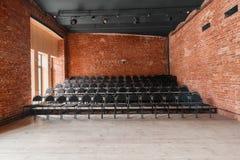 Vindstil Hall med svartstolar för webinars och konferenser Ett enormt rum med stora Windows som omges av murverk arkivfoton