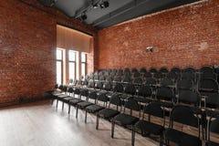 Vindstil Hall med svartstolar för webinars och konferenser Ett enormt rum med stora Windows som omges av murverk royaltyfria foton