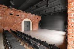 Vindstil Hall med svartstolar för webinars och konferenser Ett enormt rum med stora Windows som omges av murverk royaltyfria bilder