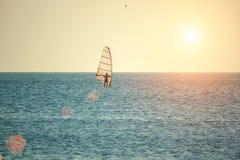 Vindsurfa på havsyttersidan på solnedgången i solen, begreppet av utomhus- aktiviteter arkivbild
