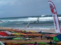 Vindsurfar seglar bräden och på stranden Royaltyfri Bild