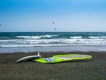 Vindsurfar seglar brädet och från stranden Arkivbilder