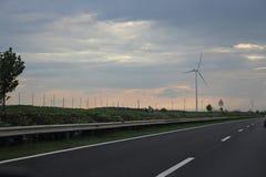 Vindturbin bredvid motorwayen arkivbild