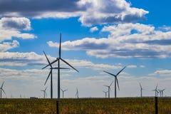 Vindturbin på Oklahoma prarie bak försedd med en hulling - trådstaketet - selektiv fokus - under blå molnig himmel royaltyfria foton