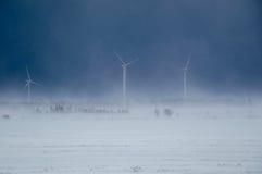 Vindturbiner för alternativ energi i en snö stormar arkivfoton