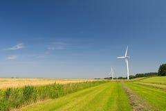 Vindturbiner i åkerbrukt landskap Arkivfoto