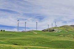 Vindturbiner på en vindlantgård på en kulle Arkivfoto