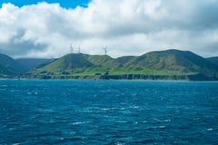 Vindturbiner på kullen från Strait Wellington för stormig kock den sydliga kustlinjen royaltyfri bild