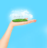Vindturbiner på äng rymmer i kvinnans hand mot blå himmel Fotografering för Bildbyråer