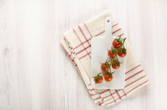 Vine of cherry tomatoes on the cutting board Stock Images